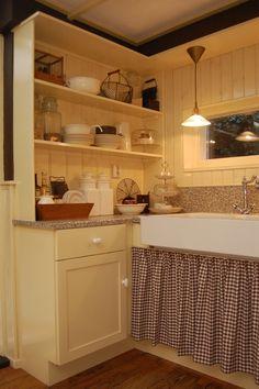 Landelijk, brocante hoek in de keuken, met leuk bruin/wit geblokt gordijntje onder de porseleinen spoelbak.