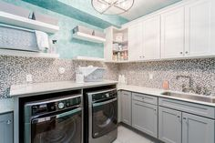 Gray and turquoise blue contemporary laundry room boasts an enclosed gray front loading washer and dryer positioned under a white countertop located beneath stacked floating white shelves mounted on turquoise blue wallpaper located above gray and white mosaic backsplash tiles.