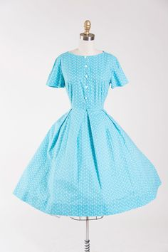 1950s vintage day dress. Made of cotton in a white heart print on an aqua blue background. Short sleeves, fitted waist, and full skirt with box pleat details. Heart shaped buttons dot bodice. Closes w