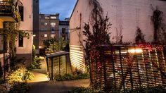 BELYSNING: På kvelden er Meyerhagen ekstra sjarmerende med en kombinasjon av direkte og indirekte belysning. På husveggene belyses klatreplantene av vegglamper og lyktestolper gir bakgården en dempet kveldsbelysning. Utelampene er fra Louis Poulsen og inngår i bakgårdens lysplan.