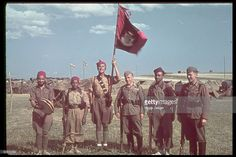Two German soldiers of the Condor Legion (at right and third right) pose with soldiers from a Moroccan unit, one of whom holds aloft a flag, at a…
