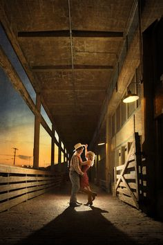 fun, evening engagement photo in Fort Worth Stockyards - bride and groom in cowboy hats and boots - fine art wedding photo by top Dallas based photographer Paul Ernest