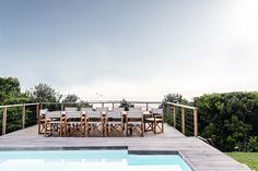 High on the mountainside overlooking Plettenberg Bay lagoon, Indigo House commands a spectacular view and boasts signature indigo, white and wood interiors. Wood Interiors, Rental Property, Garden Bridge, Pools, South Africa, Beach House, Indigo, Outdoor Structures, Vacation