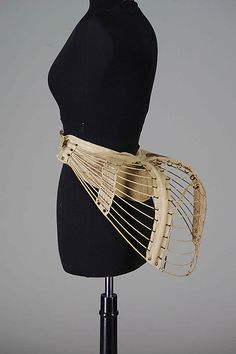 This is a linen and metal bustle of 1875-78. Bustles of the Bustle Period were worn underneath dresses to create fullness of the backside area.