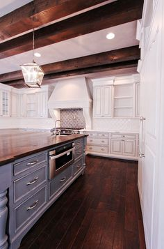 White cabinets, dark wood floors, blue grey island. But with blue grey backsplash and pale blue walls.