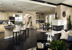 Panoramic shot of open living area including corner kitchen.
