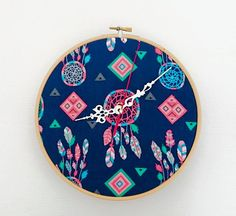This handmade wall clock is made from designer fabric and framed by an embroidery hoop. The geometric print is bright and bold and sure to catch the eye.