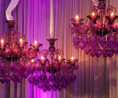 Glass globes cascade from these deep purple-hued wedding chandeliers.