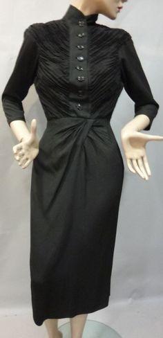 JACQUES FATH Robe de dîner, vers 1940. Crêpe de soie noir finement plissé sur le corsage manches longues boutonné devant. Plis flottants sur la jupe.Griffe blanche tissée noir: «Jacques FATH»