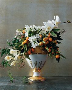 Sweet fragrances and sunrise colors fill this vase with bright promise for the New Year. Kumquats and limes evoke a tropical getaway, as do lush blossoms of phalaenopsis orchids (available at many supermarkets). The perfumes of paperwhite narcissus and jasmine are a surefire pick-me-up. As you make the arrangement, insert the sturdy citrus branches before adding the delicate flower stems. For a final touch, let some jasmine trail down the side.