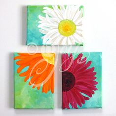 These 3 bright daisy paintings are prefect for perking up small spaces, there is one pink, one orange and one white each on a blue green background. The