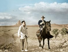 """John Ford and Tim Holt during the shooting of """"Stagecoach"""" in Monument Valley. Who is more in costume, Ford or Holt?  It's 1938, and Ford has gotten himself onto the greatest location in the history of film, and not one person in a hundred thousand who saw the film in 1939 had ever seen it before. From UA/Photofest; digital colorization by Lorna Clark."""