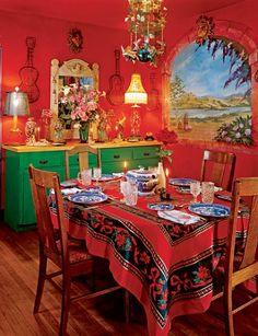 I love the bright red walls, Mexican tablecloth and art in Anjelica Huston's dining room.