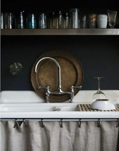 Skirted sink, elegant faucet, dark gray walls, pretty colored glasses