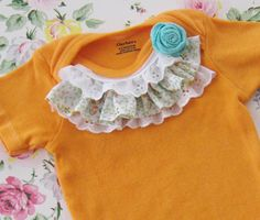 sunshine orange hand dyed onesie embellished with vintage fabric and lace, and a pretty little aqua rose, 6m to 9m, baby girl photos spring. $24.50, via Etsy.