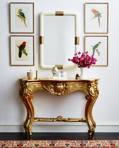 A dramatically carved and gilded console table makes for a majorly glam entryway.