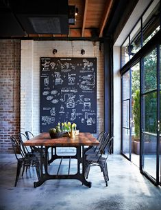 Would love to have house with a dining room like this, leading out to a patio. love the idea of a large chalkboard on an old brick wall in an industrial office space