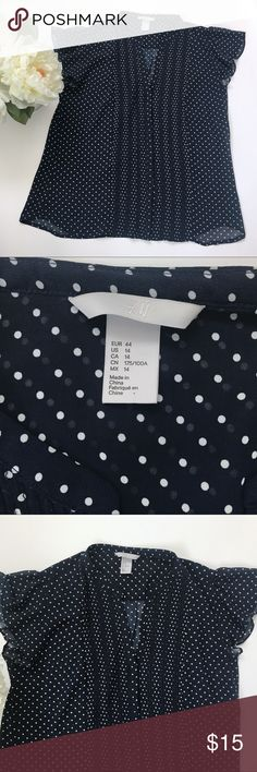 """H&M Sheer Polka Dot Blouse w Flutter Sleeve Navy blue short sleeve blouse with white polka dots from Old Navy.  Flutter cap sleeves with flattering tuxedo style pleats down the front.  Sheer button down.   Size:  14 Color:  navy with white polka dot Fabric: 100% polyester  Measurements:  Shoulders:  15"""" Chest: 21"""" Length: 24"""" at shortest, 26"""" at longest  Condition: Excellent, like new condition with no signs of use. No major flaws or imperfections. No stains, holes or heavy wear. Please see…"""