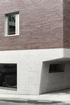 Four floors clad in slim red bricks sit above the concrete base of this office and apartment block in the South Korean city Seoul, which was designed by local firm Stocker Lee Architetti. Concrete Facade, Concrete Bricks, Concrete Architecture, Brick Facade, Facade House, Contemporary Architecture, Architecture Details, Brick Design, Facade Design