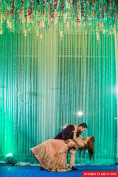 Sea green backdrop with hanging florals for a sangeet night Indian Wedding Couple Photography, Wedding Photography Poses, Pre Wedding Photoshoot, Wedding Shoot, Wedding Venues, Pool Wedding Decorations, Marriage Decoration, Backdrop Decor, Photo Backdrops