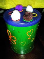 Pushing pompoms into an old yogurt container... a good activity before they are able to do the old fashioned shape sorter