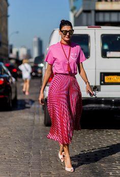 Яркие тренды уличной моды 2017: розового оттенка юбка в мелкую складку и розовая кофточка с принтом.
