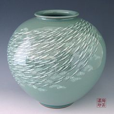 Ball Jar Celadon Green Ceramic with Fish Design    A shoal of minnows is swimming upwards on the clear jade blue stream covering the voluminous body of this celadon ceramic ball jar. The fish are vividly captured as if alive by the traditional technique of black and white slip inlaying.