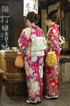 Two kimono-clad young women shopping for Japanese pickles in the Nishiki Ichiba Market in Kyoto. Text and photography by Rekishi no Tabi on Flickr