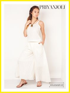 The Minimalistic Palazzo Pants are crafted from organic Cotton Khadi from the looms of Bengal; this exquisite light fabric feels like true luxury to your skin.   This well crafted pair of pleated palazzos' are clearly a hit this season. It features a comfortable waist band and pockets.Complete the look with a simple white top and lounge with friends outdoors or wear it with an ornate neck piece for a special occasion.   The pants have been styled with a cotton crop-top that is not for sale.