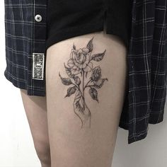 The rose in hand on thigh tattoo