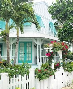 I love this white house with turquoise door and turquoise shutters and pink flowers climbing the white picket fence.