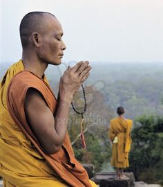 Cambodian monk praying with prayer beads on temple