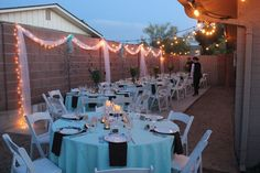 Wedding reception dinner seating area at private home. Challenge was to make a 42' x 14' RV pad a usable decorative space. Grooms hung patio cafe lights purchased from Costco for lighting. Brick fence wall was festooned with white tule and white Christmas lights. Tree decals purchased from IKEA livened up the bland wall.
