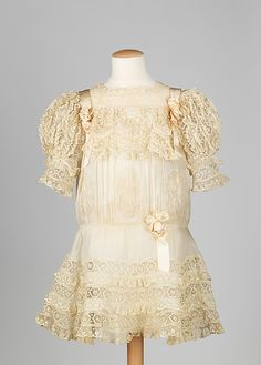 Dress  Date: ca. 1908  Featured here is a very elaborate girl's dress due to the great amount of detail which is quite typical of the Belle Époque period. The lace band has been manipulated into various ruffles, swags, sleeves and insertions, while the ribbon is manipulated skillfully into rosettes. This is an extremely refined and very opulent piece for a young girl.
