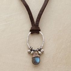 "Knotted on soft suede, a hammered sterling oval suspends a pear-shaped labradorite pendant and silver barbell beads. Sterling silver hook clasp. Imported. 15""L."