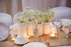 Centerpiece of painted mason jars with babies breath // image by Rachel Peters Photography