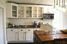 Budget Kitchen Remodel - White Country Kitchen - this post shows how to reface kitchen cabinets with inexpensive lumber. This is a cost-effective way to give your kitchen a makeover!