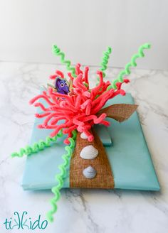 Finding Dory (or Finding Nemo) Undersea themed creative gift wrapping tutorial. Turn colorful pipe cleaners into seaweed and anemones to use instead of ribbon and bows.
