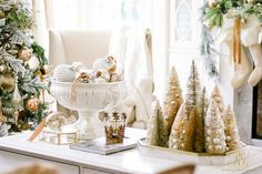 Gold and silver decorated, flocked Christmas tree in family room. Christmas coffee table with mercury glass ornaments and bottle brush trees