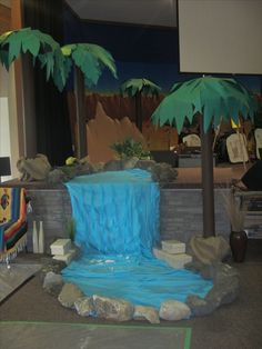 Waterfall is blue plastic tablecloth and streamers. The rocks are legit (they were heavy). Palm tree trunks are carboard tubes, and the fronds are paper taped to umbrellas.