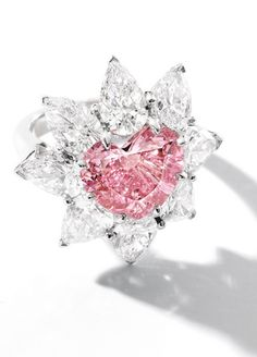 Very Rare Fancy Vivid Pink Diamond and Diamond Ring, mounted by Carvin French: Centring on a heart-shaped fancy vivid pink diamond weighing 4.57 carats, surrounded by pear-shaped diamonds together weighing 5.85 carats, mounted in platinum, signed. Ring size: 6
