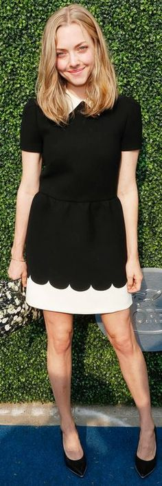 Who made  Amanda Seyfried's black print clutch handbag and white short sleeve scallop dress?