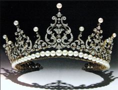 A popular tiara of the Kent family is the diamond festoon. 'Possibly' a gift from the Duke of Kent to his bride, Princess Marina,  when they married in 1934. What happened to the tiara between it's possible date of manufacture, circa 1900, and it being gifted to Princess Marina is unknown. Designed as seven diamond foliate motifs in a 'lyre-shape', topped with button pearls, with smaller diamond and pearl spacers, rising from a band of gold held slightly above a row of pearls and a velvet…