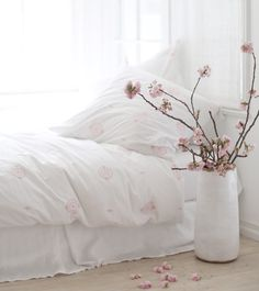 Dream a little dream.  Clean white bedding with pink accents.