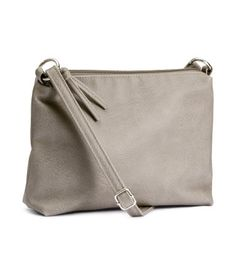 Small shoulder bag in imitation leather with narrow, adjustable shoulder strap. Zip at top. Lined. Size 7 x 10 1/4 in.