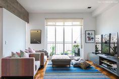 Sala de estar tem sofás, tapetes e almofadas estampadas que criam um clima leve ao ambiente.