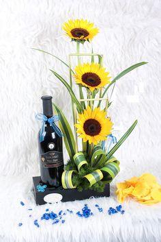ARREGLO PERFECTA COMBINACION (Código A009) Consta de tres girasoles con verde, toques amarillos más una botella de vino tinto, todo en base de madera negra. Combinación  Valor: $ .24.990