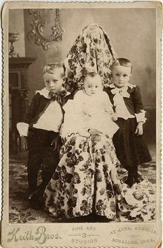 """In the 19th Century having a photograph taken was a lengthy process. Frustrated by the difficulties of getting children to sit still long enough to snap a proper photo , photographers in the 1800's conceived of a technique called """"The Hidden Mother"""". Draping a sheet over the mothers head in an attempt to camouflage her as a part of the furniture to better emphasize the child, the mother was then able to hold her infant and keep them still long enough for the camera to get an exposure."""
