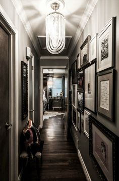 Dark wood floors, gray walls and art make this a great hallway. all the king's houses & all the king's men