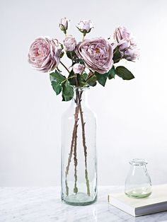 Displayed in our Tall Recycled Glass Vase, our set of three large dusty pink cabbage roses look so realistic you'll find it hard to believe they're not. With long stems featuring faux thorns and green leaves, each stem can be trimmed and bent to any size and shape. These soft pink cabbage roses will add a fresh botanical feel to your home all year around.